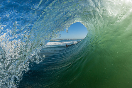 Ocean wave swimming surfer tube ride angle of upright vertical crashing wall of water energy beauty and power