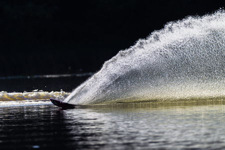 water  skier: Slalom water skier turn creating upright water wall contrast in morning light Stock Photo