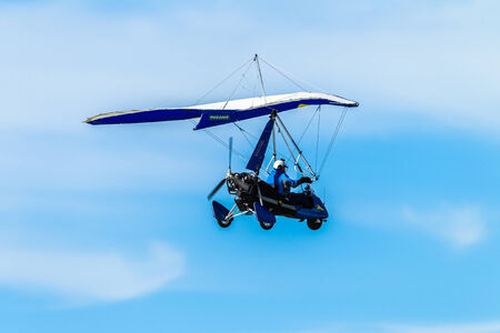 Microlight Aircraft pilot flying blue sky