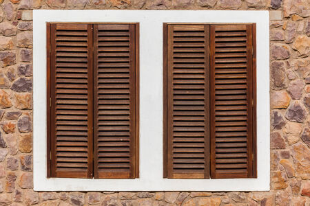 security shutters: Window wood shutters closed with ventilation and security on bedroom window Stock Photo