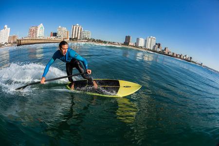 Surfen Surfer paardrijden sup board water actie close up op North Beach Durban Stockfoto