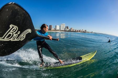 Surfen Surfer sup board water actie close up op North beach Durban