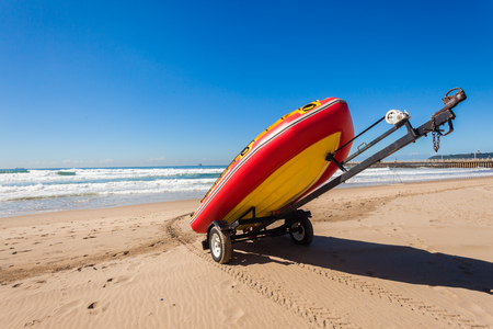 Lifeguard equipment surf inflatable boat and trailer  on ocean beach sands for rescue emergancy photo