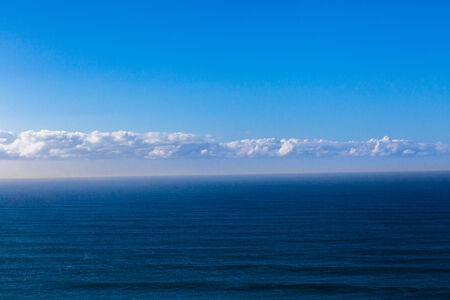 swells: Overlooking blue landscape of ocean sea swells with clouds on horizon