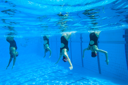 Girls Synchronized swimming in water action