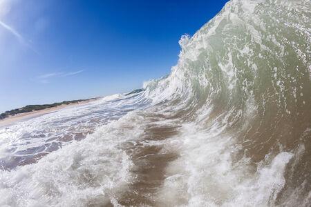 shorebreak: Ocean waves crashing shorebreak on beach coastline Stock Photo