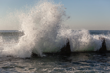 Ocean white water from wave crashing water power into tidal pool wall Stock Photo
