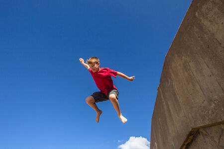 Teen boy jumping off wall in parkour on beach