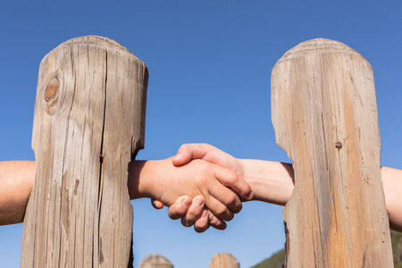 Handshake abstract form through wood poles for distant agreement barrier