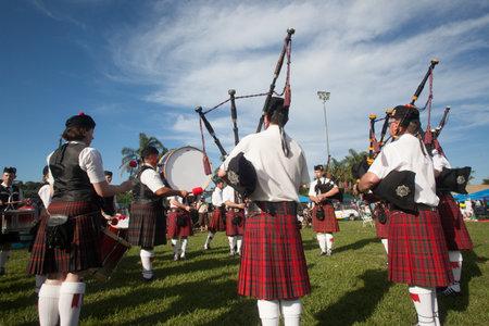 gaita: Bandas escocesas los hombres y las mujeres tocan instrumentos musicales en los colores tradicionales de la Scottish Highland Encuentro