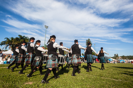 Scottish Bands men and women play musical instruments in traditional colors at the Scottish Highland Gathering