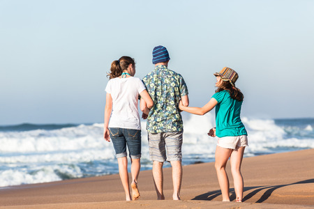 Teenagers boy girls walking together on beach with ocean waves talking holidays  photo