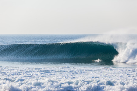 Ocean blue wave wall crashing with surfer diving escape danger beating leaving surfboard