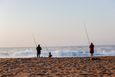 Fishermen surf fishing on beach early morning with river mist out on ocean sea wave waters