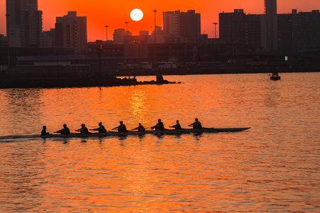 eights: Equipo de Regata de Remo Ocho colores silueteado en la salida del sol en el puerto de campo de regatas de agua en el Durban Rowing Club Jefe de la Regata Bah�a de Durban Sud�frica 12 de julio 2014