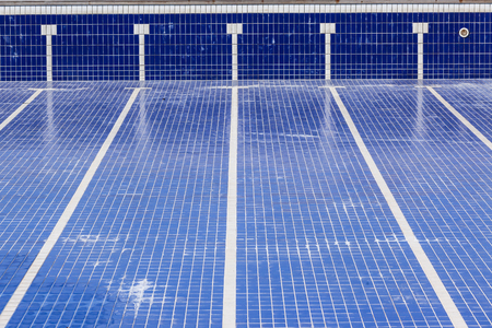 Swimming pool with blue tiles with swim lane tile markings empty of water for maintenance