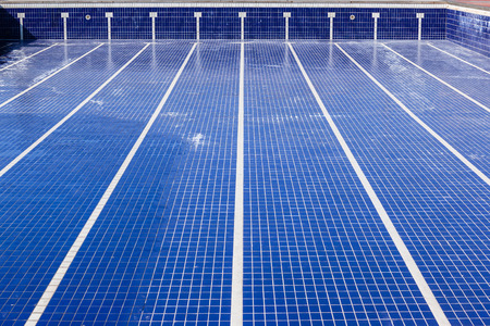 Swimming pool with blue tiles with swim lane white tile markings empty of water for maintenance Stock Photo