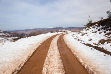mud and snow: High Mountain dirt road snow vehicle tracks