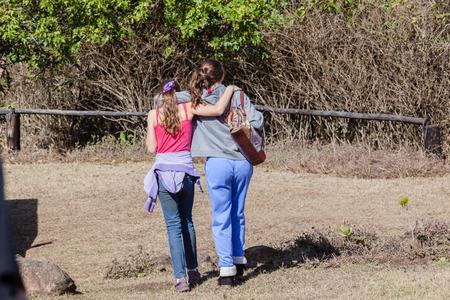 unidentified: Adolescentes joven caminando lejos juntos hablando cuidado no identificado
