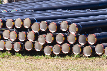dozens: Water pipes dozens lay stacked ready for installation on new aqua-duct construction project. Stock Photo