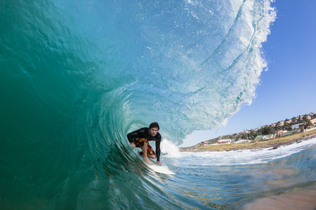 Surfing Surfer rides inside hollow blue ocean wave tube ride , closeup water photo Stockfoto