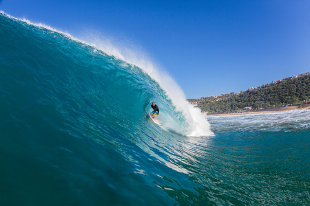 Surfing surfer tube rides inside large blue water ocean wave Stock Photo - 32705371