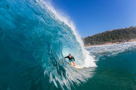 Surfing surfer tube rides inside large blue water ocean wave