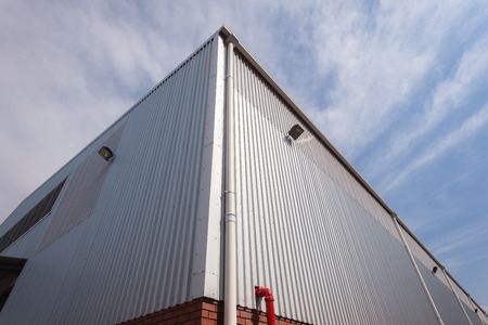Corner of factory warehouse building built with metal  structure with ibr roofing cover sheeting and brick block walls Stock Photo