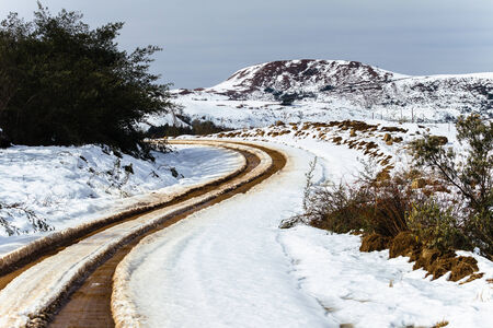 high plateau: Dirt road tracks over  high plateau mountain terrain in winter snow scenic landscape