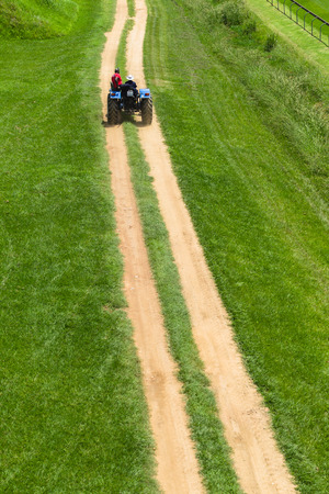road and path through: Driver driving tractor up dirt road path through green grass fields