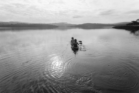 canoe paddle: Holiday fishing boy girl in canoe paddle out on smooth dam water in morning light black white contasts Stock Photo