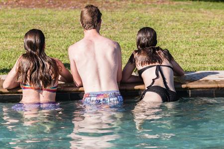 swimming pool home: Teenagers girls boy hangout summers day at swimming pool home talk laugh playtime Stock Photo