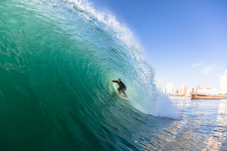 Surfing surfer rides inside hollow tube ocean wave