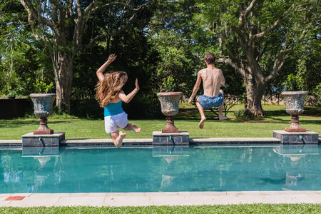 playtime: Teenagers boy girl jumping into swimming pool home summer playtime
