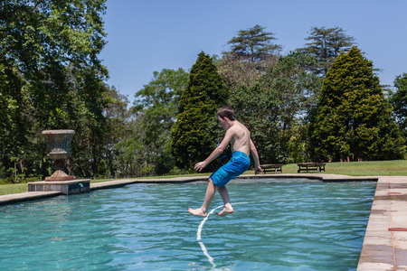 playtime: Boy jumping into swimming pool summer playtime Stock Photo