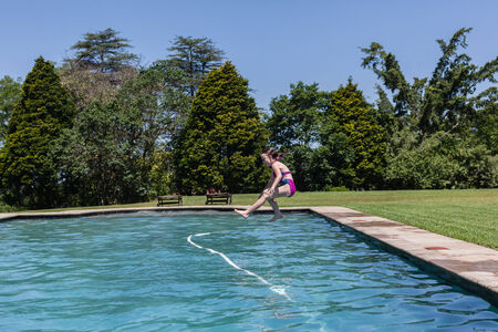 playtime: Girl jumping diving into swimming pool summer playtime