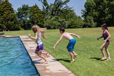 swimming pool home: Boy girls playing swimming pool  home summer playtime