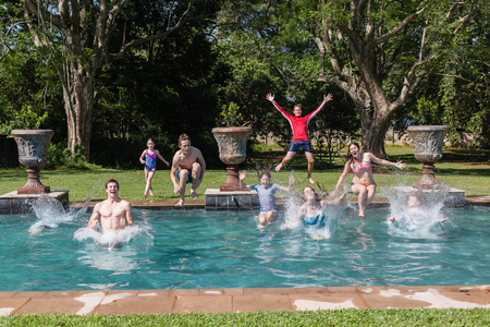 playtime: Teenagers boys girls running jumping into swimming pool summer playtime Stock Photo