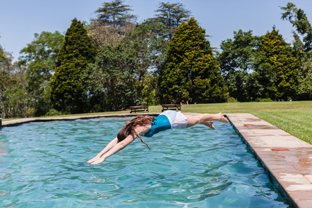 swimming pool home: Girl teenager diving into swimming pool home summer