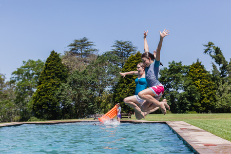 swimming pool home: Girls teenagers jumping into swimming pool home summer