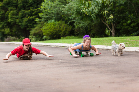 driveway: Girl skateboarding home driveway with dogs Stock Photo