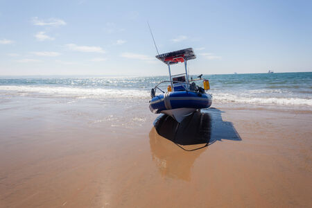 outboard: Fishing rubber inflatable boat resting on beach sand ocean sea waters