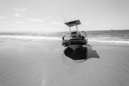 motor launch: Fishing rubber inflatable boat resting on beach sand ocean sea waters in vintage black and white tone