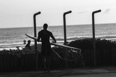 showers: Surfer in beach showers silhouetted in black white vintage tones