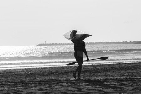 paddler: Surfski paddler carry water craft silhouetted in black white vintage tones