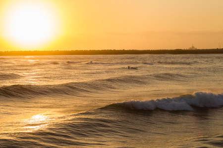 paddler: Surf-ski paddler at sunrise training on ocean waves waters around shallow reefs.