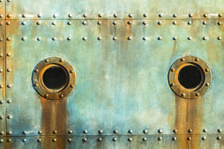 Old ship cabin porthole window with deck metal plate rivets detail background decor in era of ocean transport.