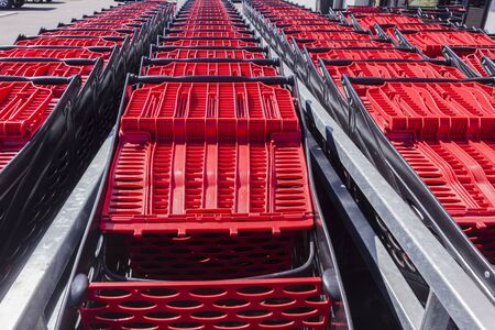 red on black: Shopping red black plastic trolleys stacked for customers usage.