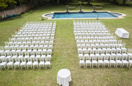 positioned: White chairs dozens positioned on grass lawn outdoors for private wedding occasion. Stock Photo