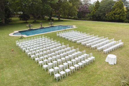 dozens: White chairs dozens positioned on grass lawn outdoors for private wedding occasion. Stock Photo